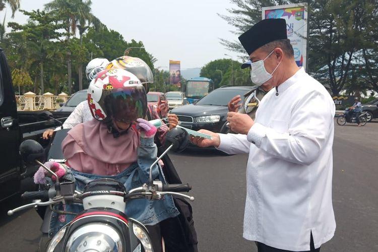 Wakil Gubernur Sumbar Nasrul Abit membagikan masker ke pengendara sepeda motor di depan Kantor BPBD Sumbar, Jalan Sudirman Padang, Jumat (13/9/2019)