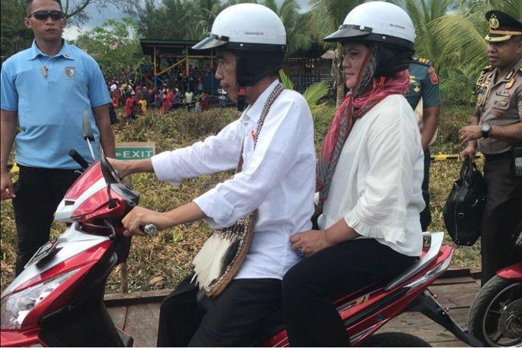 Presiden Joko Widodo memboncengi Ibu Negara Iriana saat blusukan di Kota Agats, Kabupaten Asmat, Provinsi Papua, Kamis (12/4/2018).