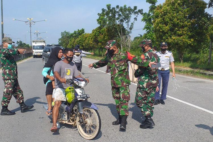 Petugas memberhentikan salah satu pengendara sepeda motor membawa penumpang tidak memakai masker saat menuju arah Kota Pekanbaru yang telah menetapkan PSBB dalam rangka mencegah wabah Covid-19, Jumat (17/4/2020). Pemeriksaan pengendara dilakukan di perbatasan Pekanbaru-Kampar jalan lintas Riau-Sumbar.