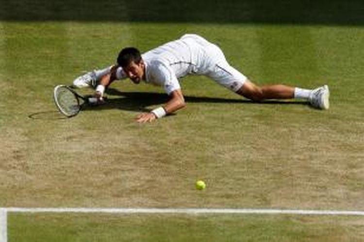 Petenis Serbia, Novak Djokovic, terpeleset dan jatuh saat berusaha mengembalikan bola Juan Martin del Potro dari Argentina, pada laga semifinal turnamen Grand Slam Wimbledon, Jumat (5/7/2013).