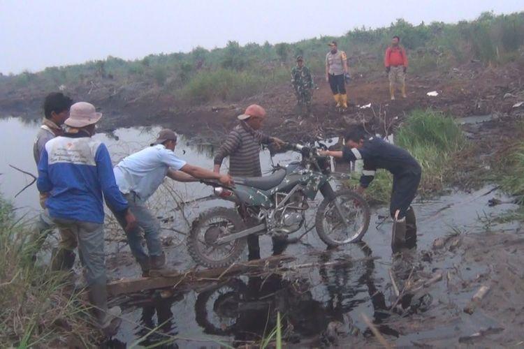 Sepeda motor harus diangkat beramai-ramai supaya bisa menyeberangi kanal di lokasi kebakaran lahan gambut di lokasi PT Rambang Teloko Ogan Komering Ilirf