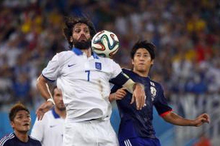 Striker Yunani, Georgios Samaras (kiri) saat berduel udara dengan bek Jepang, Arsuto Uchida, pada matchday kedua Grup C Piala Dunia 2014 di Dunas Arena, Natal, Kamis (19/6/2014).