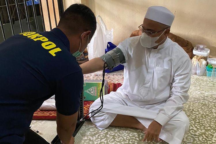 Petugas Bidokkes Polda Metro Jaya tengah mengecek kondisi kesehatan pimpinan Front Pembela Islam (FPI), Rizieq Shihab.