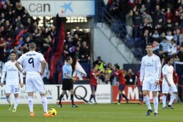 Striker Real Madrid, Karim Benzema (2 dari kiri) dan Cristiano Ronaldo (kanan), hanya terdiam melihat para pemain Osasuna merayakan gol pertama yang dicetak saat mereka menjamu Madrid di ajang Liga Spanyol, Sabtu (14/12/2013).