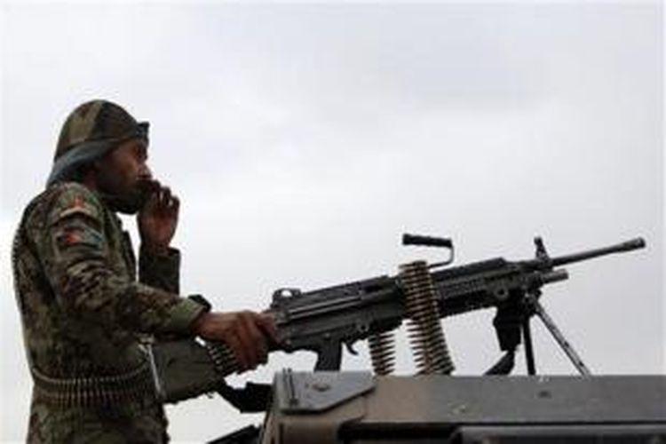 Seorang prajurit Afganistan berjaga dengan senjata beratnya di kawasan pegunungan di luar ibu kota Kabul.