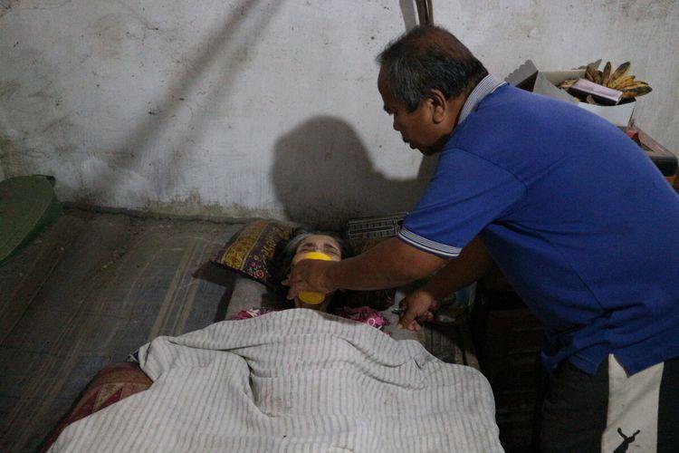 Koestomo (59), telaten merawat istrinya yang mengalami sakit dan lumpuh sejak 19 tahun lalu. Bersama keluarganya, tukang sepatu ini tinggal di Dusun Bandung Krajan, Desa Bandung, Kecamatan Diwek, Kabupaten Jombang, Jawa Timur.