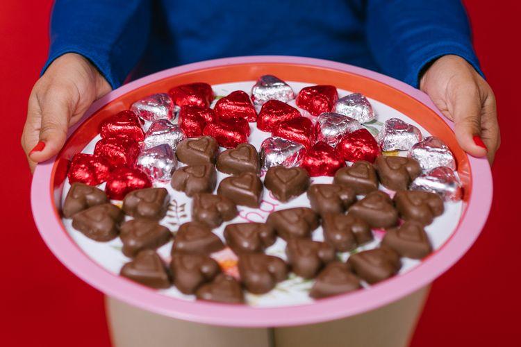 Ilustrasi cokelat berbentuk hati yang tengah dipenggang.