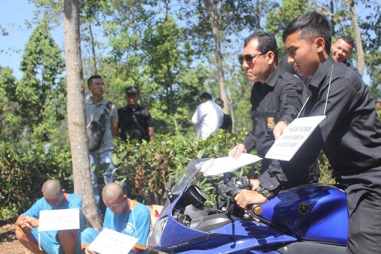 Korban, yang diperagakan seorang anggota polisi memeragakan sedang menaiki sepeda motor saat tiba di lokasi kejadian sebelum tewas dibunuh