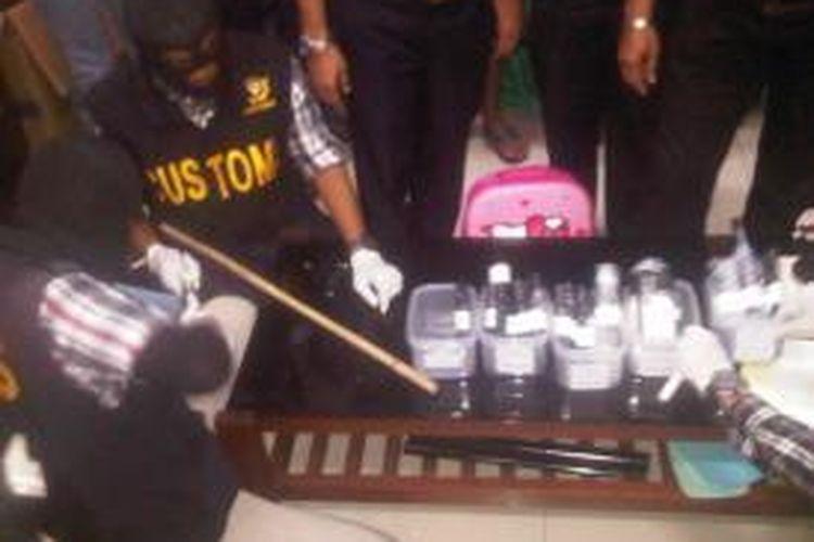Petugas Bea Cukai membongkar gagang tas berisi sabu-sabu.