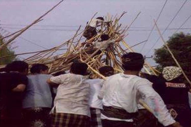Meski berbahaya, dua pemuda yang berdiri di atas gunungan kayu ini tetap antusias melestarikan tradisi Mekotek di Desa Munggu, Mengwi, Badung, Bali, setiap Hari Raya Kuningan.