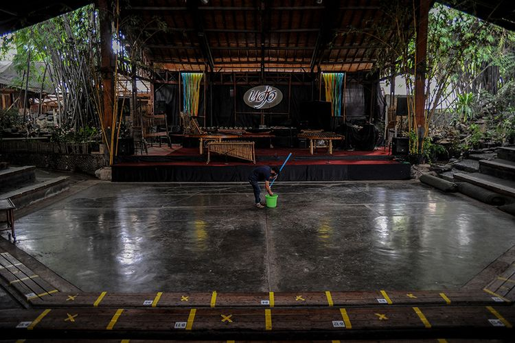 Pekerja membersihkan lantai aula pertunjukan Saung Angklung Udjo, Bandung, Jawa Barat, Minggu (24/1/2021). Pandemi membuat aktivitas bisnis pariwisata di Saung Angklung Udjo cukup terpuruk dengan hanya dikunjungi tak lebih dari 20 orang dalam sepekan, padahal saat kondisi normal mampu menarik hingga dua ribu orang per hari.