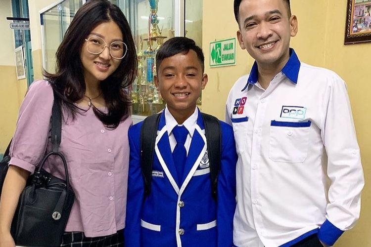 Betrand Peto diapit kedua orangtua asuhnya Ruben Onsu dan Sarwendah yamg mengantarkan ke sekolah hari pertama.