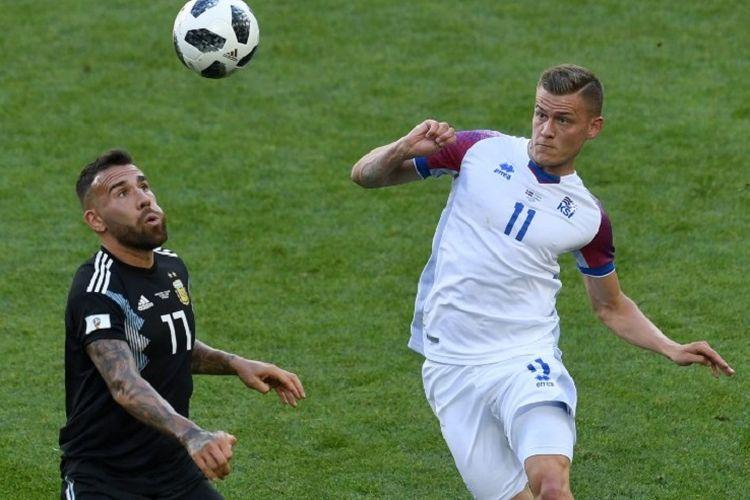 Nicolas Otamendi dan Alfred Finnbogason mencoba menyundul bola pada pertandingan Argentina vs Islandia di Stadion Spartak, 16 Juni 2018.
