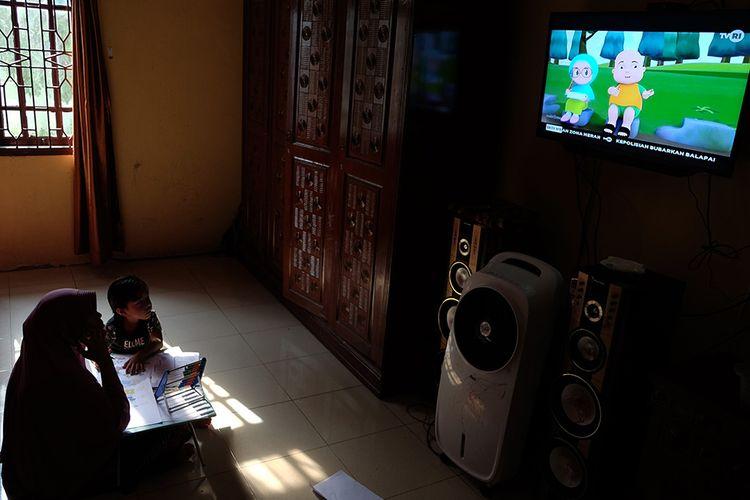 Seorang anak didampingi ibunya belajar dengan melihat tayangan siaran TVRI di rumah mereka, di Deli Serdang, Sumatera Utara, Senin (13/4/2020). Kementerian Pendidikan dan Kebudayaan bekerja sama dengan lembaga penyiaran publik TVRI sejak Senin (13/4) hingga tiga bulan ke depan menyiarkan program belajar bagi siswa mulai dari tingkat pendidikan anak usia dini (PAUD) hingga SMA guna membantu para siswa belajar di rumah selama wabah COVID-19.