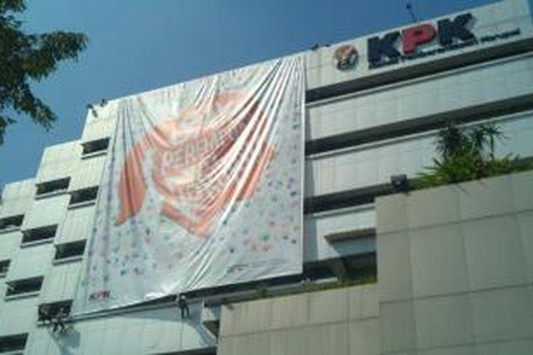Enam perempuan menuruni Gedung KPK menggunakan tali untuk membentangkan spanduk raksasa bertuliskan