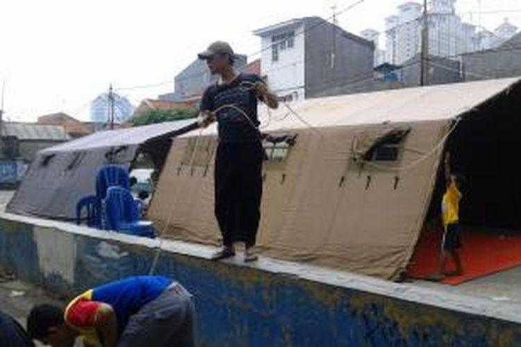 Seorang warga tengah menyambung kabel untuk menyalakan listrik di dua tenda bagi korban kebakaran Tanjung Duren, Jakarta Barat, Kamis (13/11/2014).