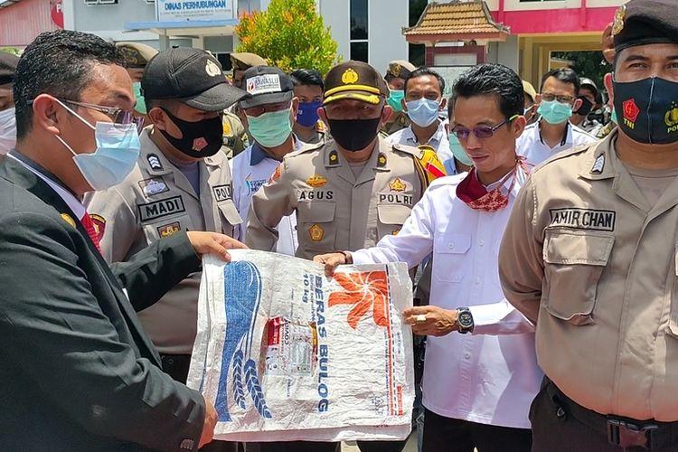 Koordinator Aksi Yongki Ariansyah menyerahkan barang bukti berupa kemasan karung beras bergambar bupati petahana Ilyas Panji Alam ke Ketua Bawaslu Ogan Ilir Dermawan Iskandar