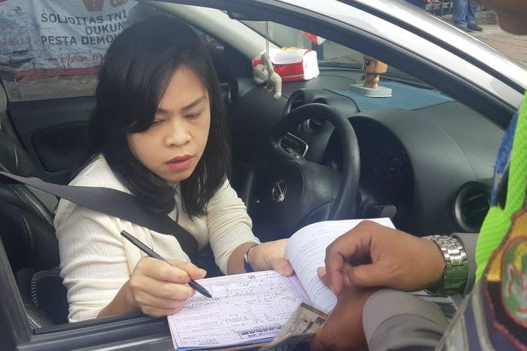 Seorang pengendara di tilang di Traffic Light Tomang Raya, karena melanggar peraturan ganjil genap pada Senin (9/9/2019)