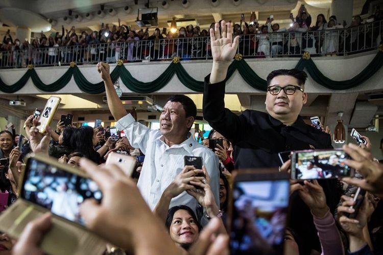 Peniru Presiden Duterte, Cresencio Extreme (tengah) dan peniru Kim Jong Un, Howard X, saat muncul di gereja St Joseph, di Hong Kong, Minggu (3/2/2019).