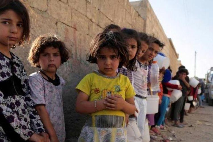 Anak Suriah mengantre makanan di utara Kota Raqqa, selama bulan suci Ramadhan, 14 Juli 2013. Kepala Koalisi Nasional Suriah Ahmad al-Assi telah mendukung seruan untuk gencatan senjata selama bulan suci Ramadhan dari Sekjen PBB Ban Ki-Moon.