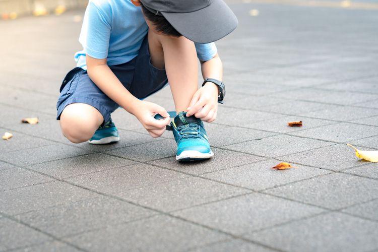 Anak memakai sepatu.