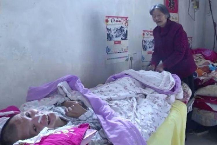 Wang Shubao (48) tersadar dari kondisi koma yang sudah dilaluinya selama 12 tahun. Di ujung tempat tidur terlihat Wei Mingying (75), sang ibu yang merawatnya selama ini.