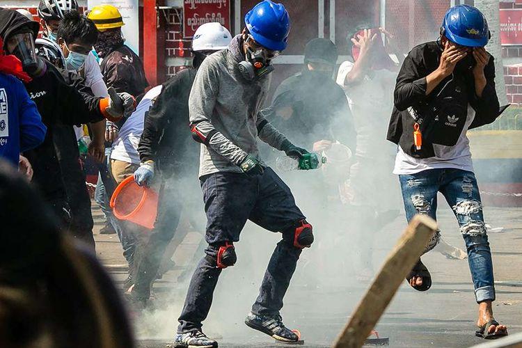 Para pengunjuk rasa berlari setelah gas air mata ditembakkan oleh polisi yang mencoba membubarkan mereka selama demonstrasi menentang kudeta militer di Yangon, Myanmar, Minggu (28/2/2021). Sedikitnya 18 orang tewas dan 30 lainnya terluka dalam aksi demonstrasi di Myanmar pada 28 Februari, serta disebut sebagai hari paling berdarah dalam serentetan aksi protes menentang kudeta militer.
