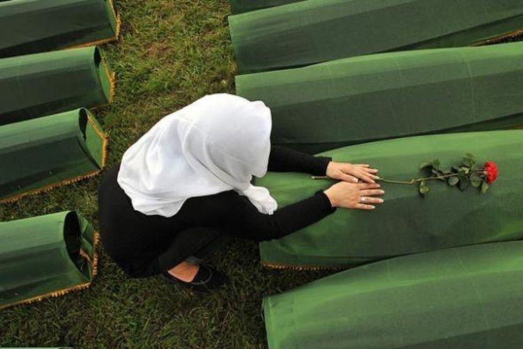 Seorang perempuan Muslim Bosnia yang selamat dari pembantaian Srebrenica 1995, meratapi peti mati yang berisi sisa jasad kerabatnya yang tewas dalam tragedi kemanusiaan terburuk di Eropa pasca-Perang Dunia II.
