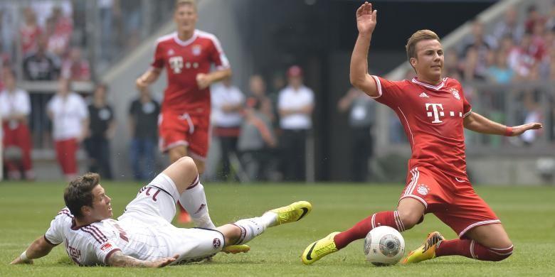 Pemain Nuremberg, Daniel Ginczek (kiri), melanggar gelandang Bayern Muenchen, Mario Goetze, dalam pertandingan Bundesliga.