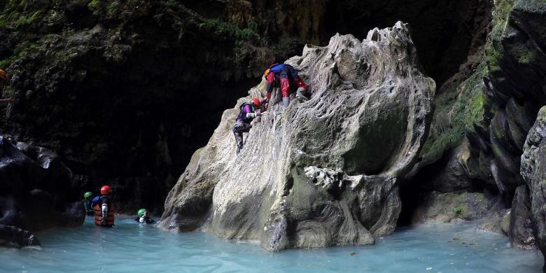 Beberapa peserta cave tubing berusaha memanjat salah satu batu yang terdapat di bagian Goa Kalisuci, Gunungkidul, DI Yogyakarta untuk berpose di goa yang eksotis tersebut.