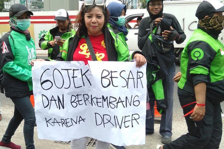 Salah satu pengedara ojol menunjukkan poster bertuliskan Gojek Besar dan Berkembang Karena Driver. Hal tersebut dilakukan saat pengemudi Gojek menggelar aksi di depan gedung Kedubes Malaysia, Jalan Rasuna Said, Jakarta Selatan, Selasa (3/9/2019)