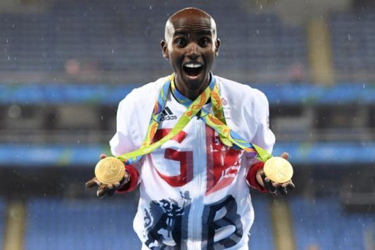 Pelari Inggris Raya, Mo Farah, berfoto dengan dua medali emas Olimpiade Rio yang dimenanginya dari lomba lari nomor 5.000 meter dan 10.000 meter di dekat podium juara di Olympic Stadium, Rio de Janeiro, Brasil, Sabtu (20/8/2016).