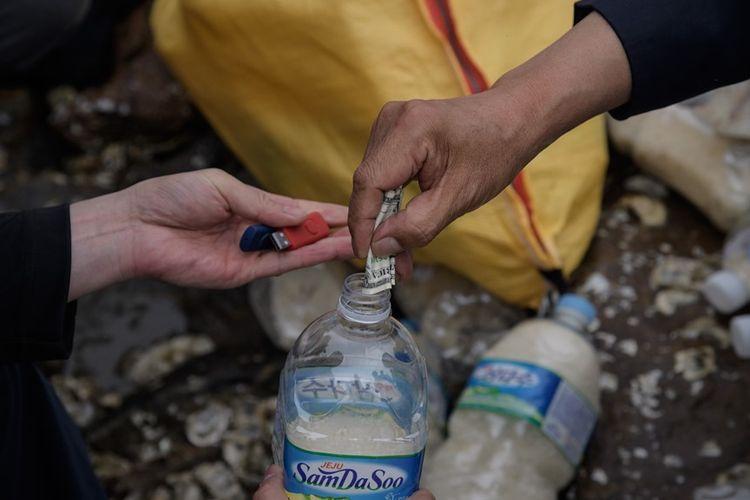 Aktivis pembelot Korea Utara memasukkan beras, uang dan stik memori ke dalam botol sebelum dilemparkan ke laut oleh para aktivis pembelot Korea Utara dari pulau Ganghwa di barat Seoul, Selasa (1/5/2018).