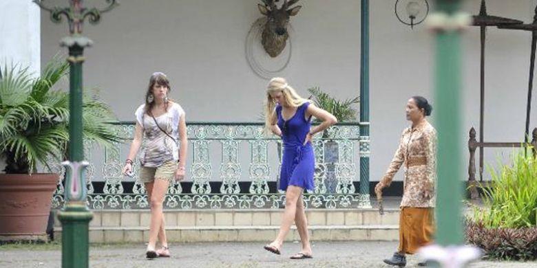 Pemandu wisata (berbaju batik) mengantarkan wisatawan asing berkeliling Keraton Yogyakarta, Yogyakarta, Senin (31/1/2011).