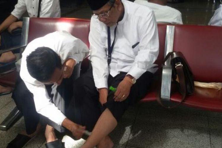 Jokowi tengah mengoleskan balsem cair ke betis mantan Ketua Umum PBNU Hasyim Muzadi yang kelelahan usai umroh saat transit di Bandara Madinah, Senin (7/7/2014).