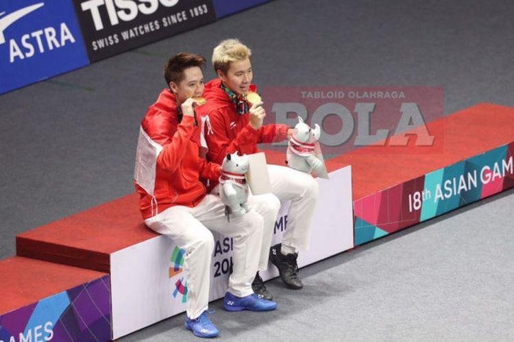 Marcus Fernaldi Gideon (kanan) dan Kevin Sanjaya Sukamuljo (kiri) memegang medali emas usai menjuarai cabang bulu tangkis nomor ganda putra Asian Games 2018, Selasa (28/8/2018).
