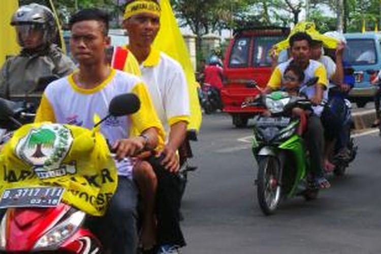 Massa pendukung Golkar yang melintasi Jalan Raya Bogor, depan lokasi GOR Ciracas tempat Golkar melakukan kampanye di Jakarta Timur. Selasa (18/3/2014).