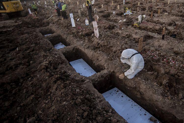 Petugas pemakaman mengumandangkan azan di pusara di TPU Rorotan, Cilincing, Jakarta, Minggu (4/7/2021). Jumlah kematian akibat COVID-19 per hari Minggu (4/7/2021) mencapai 555 kasus, yang menjadi rekor tertinggi sejak kasus pertama COVID-19 di Indonesia diumumkan Presiden Joko Widodo pada awal Maret 2020.  ANTARA FOTO/Muhammad Adimaja/aww.