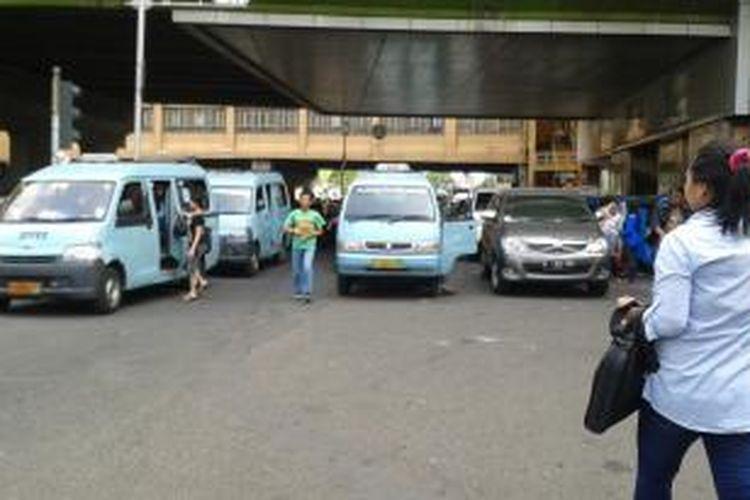 Kondisi jalan jam 14:30 di depan pasar Blok A Tanah Abang, Jakarta Pusat, Selasa (14/10/2014). Mobil angkot yang ngetem menutupi dua lajur di jalan tersebut yang menyebabkan kendaraan pribadi kesulitan untuk lewat.