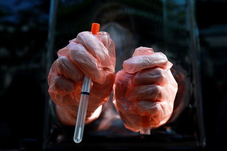 Petugas medis menggunakan sarung tangan pelindung menunjukkan test kit saat bekerja di laboratorium berjalan untuk uji virus corona (COVID-19) di Bangkok, Thailand, Kamis (9/4/2020).ANTARA FOTO/ REUTERS/Soe Zeya Tun/AWW/djo