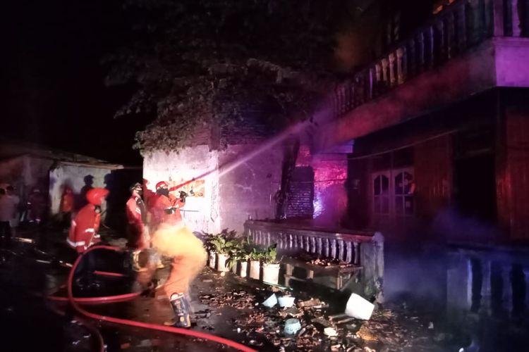 Petugas memadamkan api yang membakar rumah sekaligus pabrik tahu.