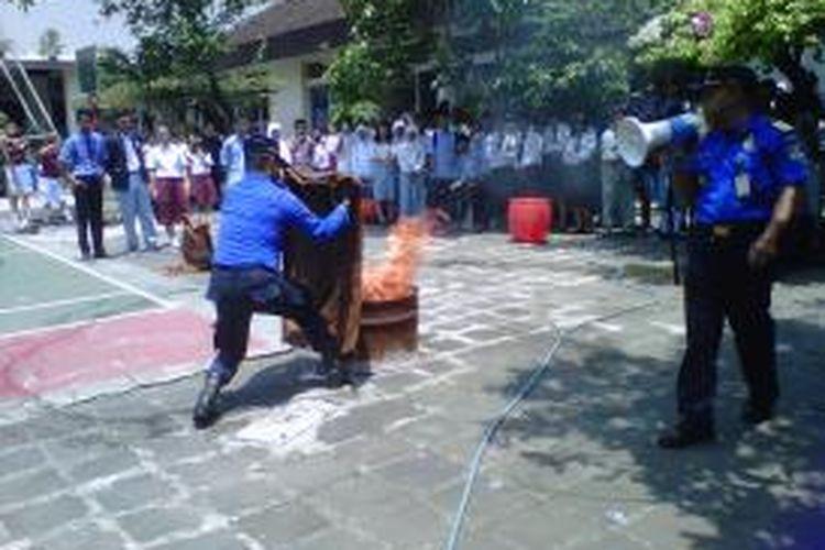 Tim UPTD Pemadam Kebakaran Kota Magelang sedang memberi contoh bagaimaa memadamkan api dengan cara tradisional, di SMK Pius Kota Magelang, Kamis (12/9/2013).
