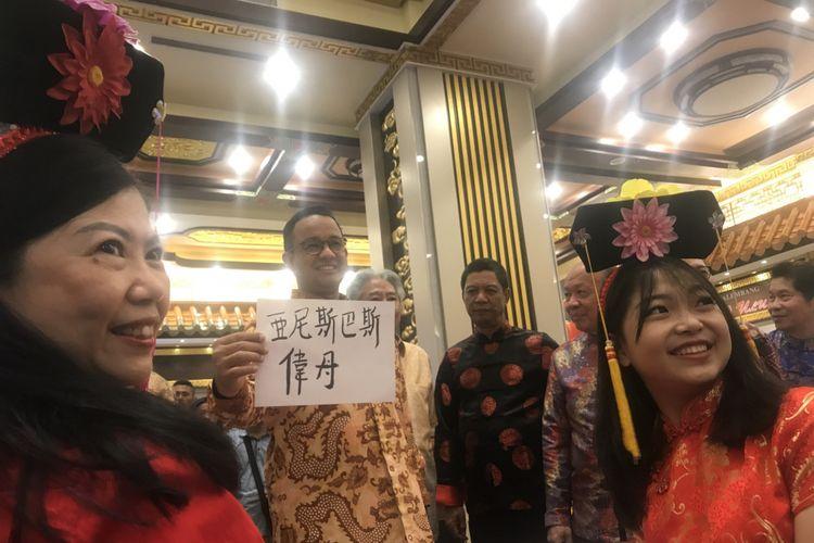 Gubernur DKI Jakarta, Anies Baswedan, berfoto dengan membawa cinderamata bertuliskan huruf Tionghoa, Selasa ( 19/2/2019) di China Town Point, Glodok, Jakarta Barat, dalam Festival Pecinan 2019.
