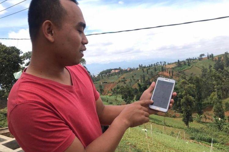 Ujang Margana (27) petani asal Cimenyan Kabupaten Bandung memperlihatkan aplikasi yang digunakannya dalam sistem irigasi otomatis. Dengan aplikasi tersebut, Ujang bisa menyiram kebunnya dimanapun.