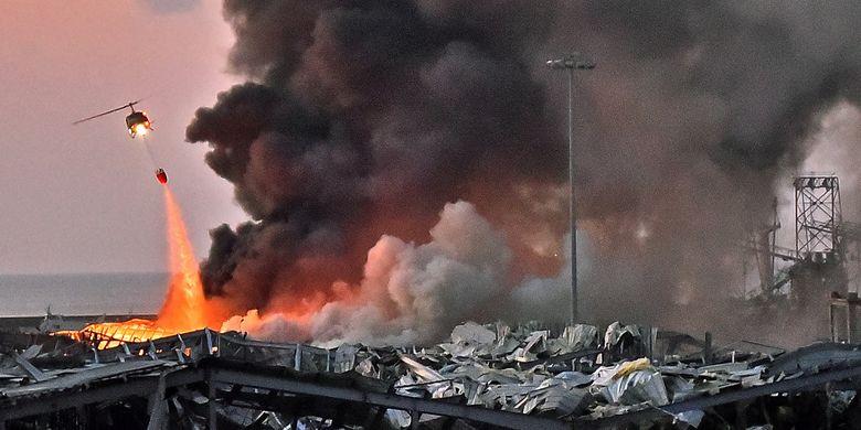 Sebuah helikopter berusaha memadamkan api dalam ledakan yang terjadi di pelabuhan Beirut, ibu kota Lebanon, pada 4 Agustus 2020.