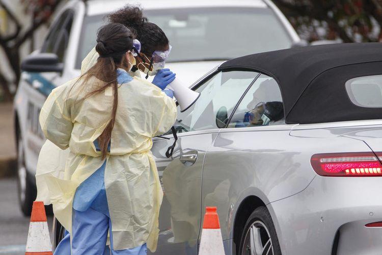 Petugas medis memandu pengendara mobil di stasiun tes Covid-19 drive-thru di Arlington, Virginia, Amerika Serikat (AS), pada 19 Maret 2020. Layanan drive-thru ini dijalankan oleh Virginia Hospital Center and Arlington Country.