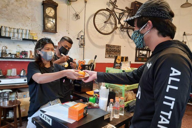Sejumlah pembeli di Kedai Kopi Klodjen Djaja Kota Malang saat membeli kopi secara gratis dengan menunjukkan sertifikat vaksin, Jumat (30/7/2021).