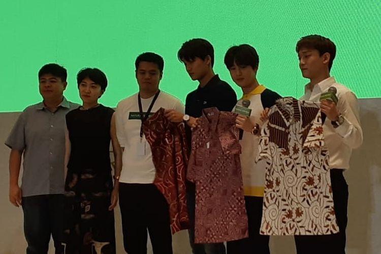 Tiga personel EXO, Kai (pakai kaos hitam), Suho (kaos putih berkerah kuning), dan Chen (kemeja putih lengan panjang) saat menerima batik dari perwakilan Nature Republic di Hotel Westin, Jakarta Selatan, Minggu (26/5/2019).