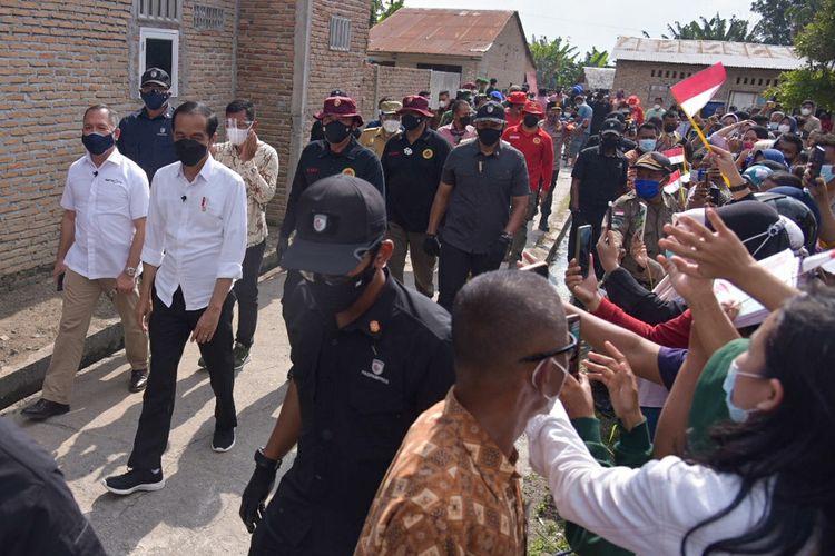 Presiden Joko Widodo (kedua kiri) berjalan menuju lokasi pelaksanaan vaksinasi COVID-19 dari pintu ke pintu (door to door) di Desa Emplasemen, Kecamatan Beringin, Kabupaten Deliserdang, Sumatera Utara, Kamis (16/9/2021). Dalam kunjungan tersebut Presiden Joko Widodo menyaksikan secara langsung pelaksanaan vaksinasi yang dilakukan secara jemput bola atau dari rumah ke rumah sehingga dapat mempercepat program vaksinasi COVID-19. ANTARA FOTO/Fransisco Carolio/Lmo/wsj.