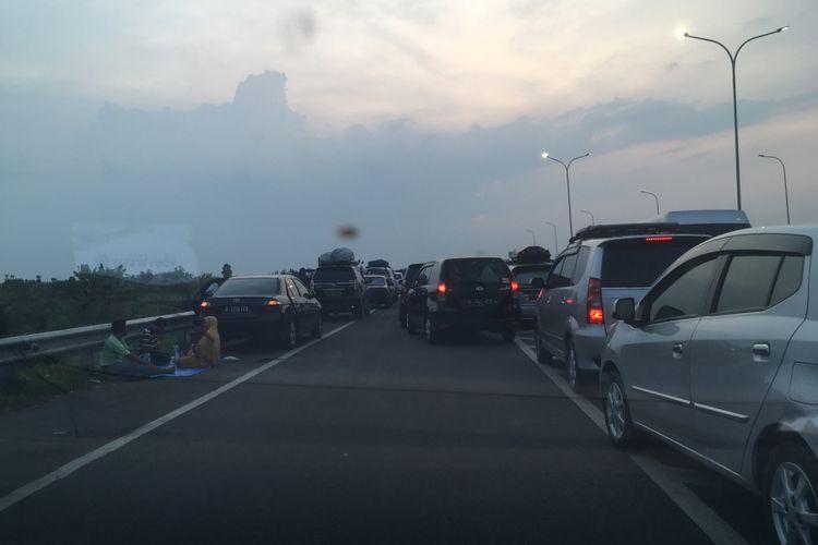 Sejumlah pemudik memilih menepikan kendaraan dan beristirahat di bahu jalan Tol Cipali, Sabtu (1/7/2017) petang. Semua tempat istirahat (rest area) di tol ini di arah menuju Jakarta penuh sesak dan tak bisa menampung lagi pelintas yang belakangan datang.